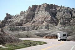 Motor home RV traveling through the Badlands National Park, South Dakota. The Badlands park is located just south of Wall, SD.  It features rocky structures stock images