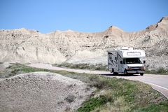 Motor home RV traveling into the Badlands National Park, South Dakota. The Badlands park is located just south of Wall, SD.  It features rocky structures that stock image