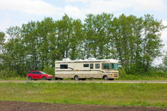 A motor home and tow car in the yukon territories Stock Photos