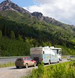 An rv and tow car in alaska. A motor-home towing a mud-caked car in the rockies Royalty Free Stock Images