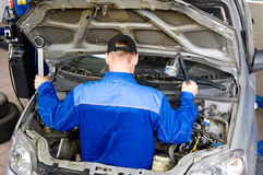 Motor mechanic. A motor mechanic repairs inside a car Royalty Free Stock Photos