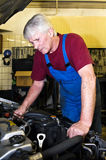 Motor mechanic. A senior motor mechanic servicing a car inside a garage royalty free stock photography