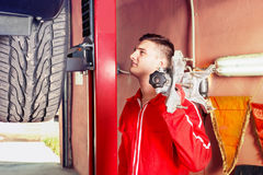 Motor mechanic holding a piece of equipment. Over his shoulder as he stands alongside the wheel of a car on a hoist in an automotive workshop looking Stock Image