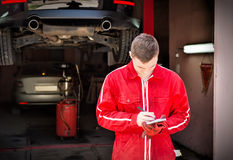 Motor mechanic standing making notes in front of a black sedan. Elevated on a hoist in a bay in a garage or workshop Royalty Free Stock Photos