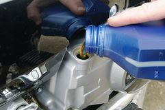 Motor oil poring. Fill oil to the engine after driving motorcycle Royalty Free Stock Image