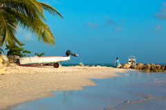 A motor, palms, a woman in blue bent on the shore of the ocean. Worthing Beach in Barbados stock images