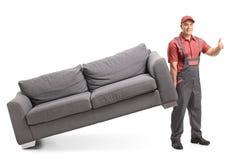 Motor que levanta um sofá e que faz um polegar acima do sinal imagem de stock