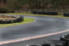 Motor Racing Track corner with tyre wall. Corner section of a tarmac motor racing track or circuit for kart racing Royalty Free Stock Photos