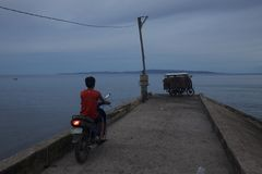 Motor-Radfahrer auf Pier bei Sonnenuntergang Stockbild