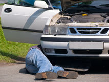 Motor Repair. Mechanic under the car, repairing the engine Royalty Free Stock Photography