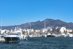 Motor and sailboats ancoring in the marina in Roses, Spain. The water is colored deep blue, while the sky has a lighter tint. In the back the start of the Royalty Free Stock Photography