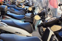 Motor Scooters, Italy. A row of practical and popular transport motor scooters parked in a busy and crowded Italian city centre Royalty Free Stock Photo