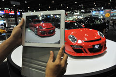 Motor Show in Bangkok. A man uses a tablet computer to photograph a RUF RT12 based on the Porsche 911 while attending the Thailand International Motor Expo on Royalty Free Stock Image