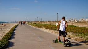 Motor Skateboard. Young men on a motor skateboard in Tel-Aviv's promenade Stock Images