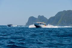 Motor boat and island in the sea Stock Photos