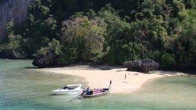 Motor speed boat tied up at rocky island coast stock video