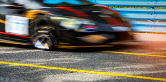 Motor sport car racing on asphalt road with blue fence and yellow line traffic sign. Car with fast speed driving and motion. Blurred. Black racing car with red royalty free stock photography