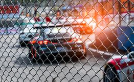 Motor sport car racing on asphalt road. View from the fence mesh netting on blurred car on racetrack background. Super racing car royalty free stock image