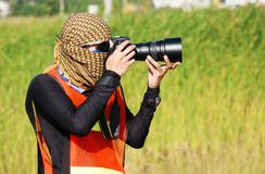 Motor sports photographer covering. The head with a cloth on a blurred green background Stock Images