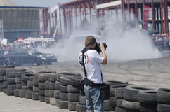 Motor-sports photographer. A professional photographer shooting a car engaged in a drift demonstration during the Bucharest Wheels Arena motor show event in Royalty Free Stock Photography