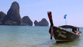 Motor thai longtail boat drifts at sea coast. With cliffy islands on background stock video footage