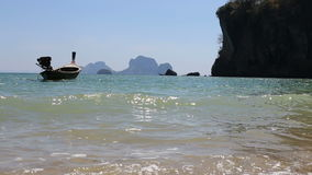 Motor thai longtail boat drifts at sea coast. With cliffy islands on background stock video
