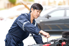 Motor vehicle mechanic. Man maintenance and checking the car engine in garage royalty free stock photo