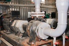 Motor viejo con una bomba conectada en la tubería del abastecimiento de agua Imágenes de archivo libres de regalías