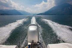 Motor y estela del barco de motor que apresuran a través del lago rodeado cerca Imagenes de archivo