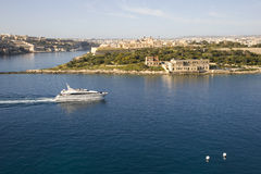Manoel Island, Marsamxett Harbour Malta. A motor yacht passes Manoel Island, Marsamxett Harbour. Mediterranean island of Malta. March 2013 Royalty Free Stock Photography