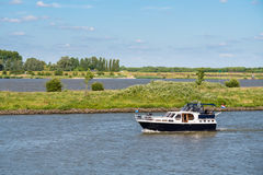 Motor yacht on river Afgedamde Maas near Woudrichem, Netherlands. Motorboat sailing on river Afgedamde Maas and Boven-Merwede near Woudrichem, Netherlands royalty free stock photo