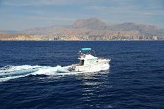 Private beautiful yacht sailing fast close to Alicante coast in Spain. Motor yacht sailing in the coast of Calpe in Alicante in a sunnt day in east coast of Royalty Free Stock Photography