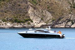 Private beautiful yacht sailing fast close to Alicante coast in Spain. Motor yacht sailing in the coast of Calpe in Alicante in a sunnt day in east coast of Royalty Free Stock Photo