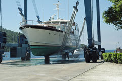 Motor yacht in sling. Luxury yacht on sling being hauled out of the water Stock Images