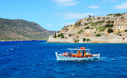 The motor yacht with tourists is near Spinalonga island Stock Images