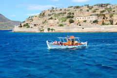 The motor yacht with tourists is near Spinalonga island Stock Photo