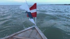 Motora en el mar con las banderas que agitan metrajes