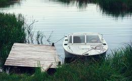 Motorbåt på de Pier Among The vasserna i en flodfjärd royaltyfria foton