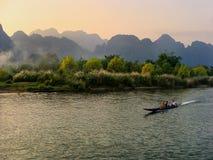 Motorbåt som är rörande på Nam Song River på susnet i Vang Vieng, Vien fotografering för bildbyråer
