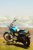 Motorbike adventure travel holiday coastline of New Zealand. A large road motorbike parked on the seaside front of the ocean beach at New Plymouth, North Island Stock Image