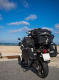 Motorbike at beach packed with camping equipment. A motorbike packed with camping equipment Stock Images