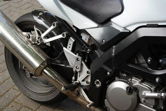 Motorbike close-up detail. Close-up of engine and rear wheel of black and silver motor-cycle Stock Photos