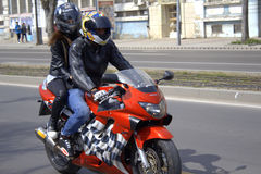 Motorbike couple. Young couple riding red Honda motorbike on city boulevard Royalty Free Stock Image