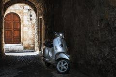 Motorbike in dark arch of Rhodes town with old wooden door on a background. Rhodes island, Greece.  Stock Photo