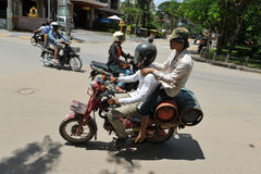Motorbike Delivery Men. Delivery workers transport gas cylinders by motorbike on July 11, 2012 in Siem Reap, Cambodia. The use of motorbikes as transport is Royalty Free Stock Images