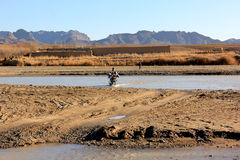 River crossing in southern Afghanistan. A motorbike drives across a river in southern Afghanistan Stock Photos
