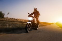 Motorbike drives on the road at sun dawn stock photos