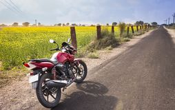 Motorbike in between fields and roads Royalty Free Stock Photography