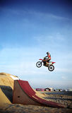 Motorbike jump. Motor biker jumping over a sand pile with deep blue sky. Film scan Stock Photography