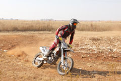 Motorbike kicking up trail of dust on sand track during rally ra Stock Image